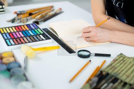 female painter drawing draft at sketchbook