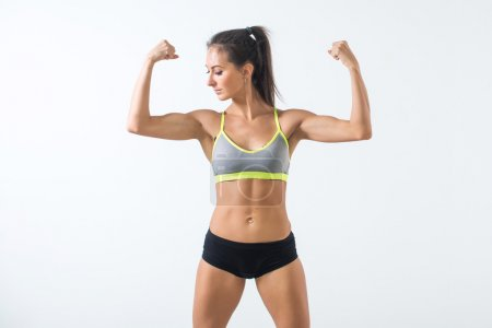 Photo for Fit woman showing biceps warming up exercising doing sports, fitness workout. - Royalty Free Image
