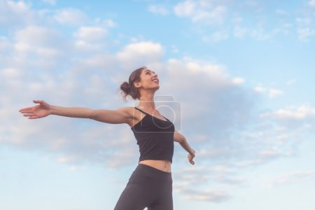 woman enjoying sunset with arms