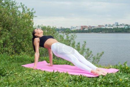 Photo pour Fit femme étirant le corps dans la pose de planche vers le haut faisant l'exercice de bordure inversée sur le parc gazon extérieur - image libre de droit