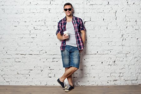 Bright young man hipster on vacation enjoying the day with coffee