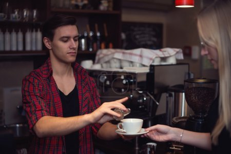 Hipster barista in  plaid shirt adds cinnamon customers cofee.