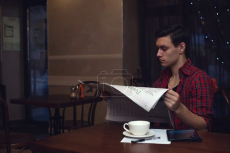 YOung hipster reading newspaper in a cafe during lunch with cup ot tea coffee.