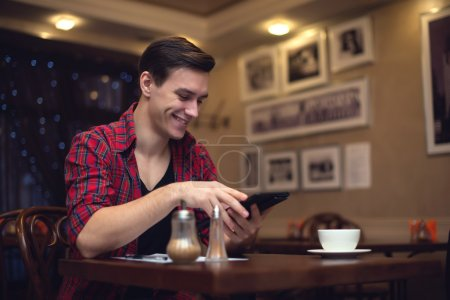 Young smiling attractive man uses his tablet in the lunchtime at cafe