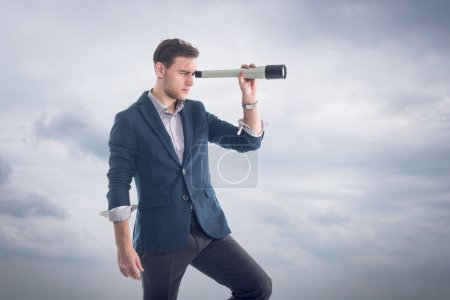 Young attractive handsome businessman standing  with clouds around and looking through the spyglass to find new perspectives.