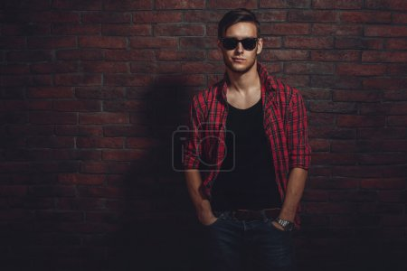Attractive young hipster smiling and standing against brick wall with hands in the pockets