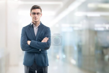 Young handsome businessman wearing glasses in the office and standing alone hands crossed.