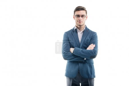 Young strong businessman  in fashionable suit stands against the wall with hands crossed.