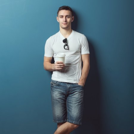 Young attractive handsome man in white t-shirt jeans denim shorts standing against the wall and smiling holding coffee.
