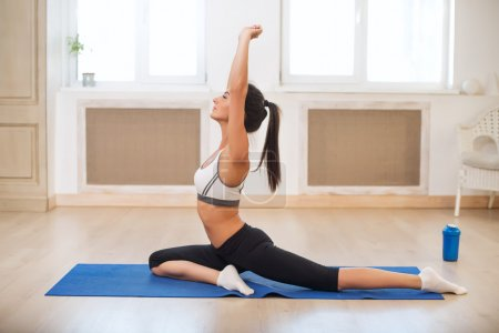 Beautiful athletic sporty woman in the gym doing exercises on blue mat raising her hands.