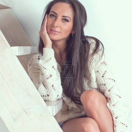 Photo for Caucasian dark-haired woman is sitting at the stairs in cozy home atmosphere with a hand on her cheeck and kind eyes - Royalty Free Image