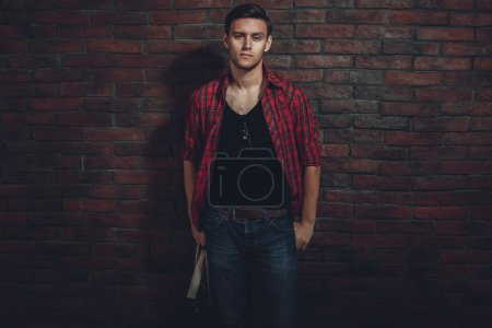 Hipster serious man casual clothes unbuttoned shirt and denim jeans standing near brick wall hand in the pocket looking at camera