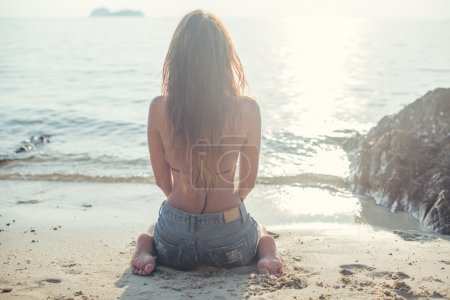 beautiful young woman in jeans shorts with resting at beach front of the sea summer sitting on sand warm colors filter instagram