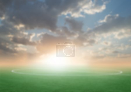 green football soccer field with the blue sky sunset blurred background