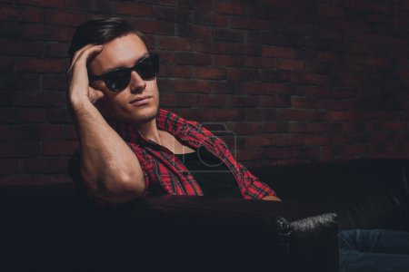 Portrait handsome young hipster man glasses casual clothes unbuttoned shirt sitting relaxing leaning on leather luxury sofa looking at the camera