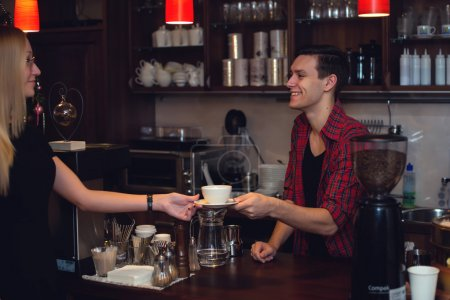 Young attractive hipster working in cafe as barista. Constant smiling providing perfect service giving order.