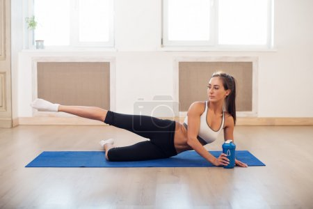 Young dark-haired athletic active sporty slim woman doing yoga exercise the gym or home stretching her legs
