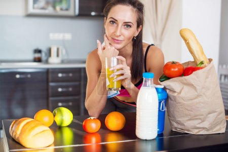 Pretty attractive athletic active sportive lady woman standing in kitchen and healthy food fresh fruits milk bread around holding glass with juice