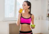 Gorgeous young athletic sportive woman in sport outfit drinking fruit juice after the training