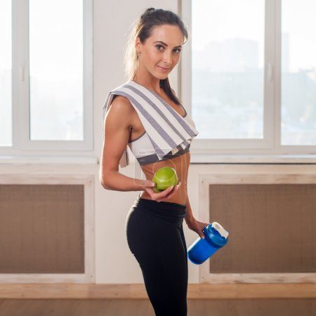 Gorgeous young athletic sportive woman in sport outfit holding apple and shaker after the training.