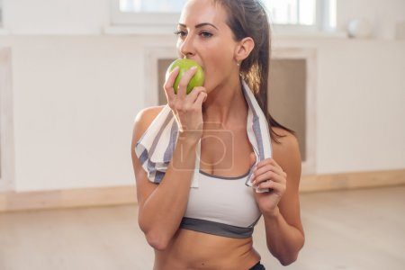 Active athletic sportive woman with towel in sport outfit eating apple after the training.