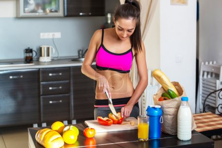 Pretty attractive athletic active sportive lady woman standing in kitchen with a towel on her shoulder and healthy food fresh fruits milk bread