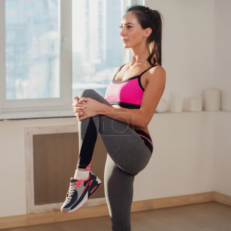 Gorgeous young athletic active sportive woman in sport outfit doing yoga exercise the gym or home