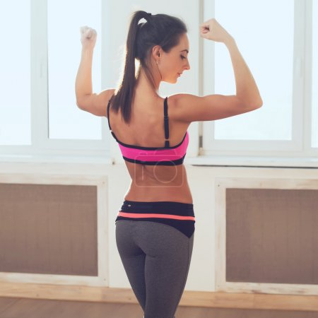 Active athletic sporty woman in sport outfit standing showing biceps muscles of the back and buttocks rear view healthy lifestyle