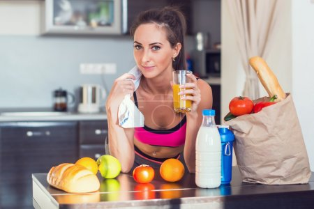 Photo for Pretty attractive athletic active sportive lady woman standing in kitchen with a towel on her shoulder and healthy food fresh fruits milk bread drinking juice - Royalty Free Image