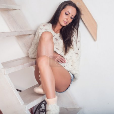 Dark-haired woman is sitting at the stairs in cozy home atmosphere looking down
