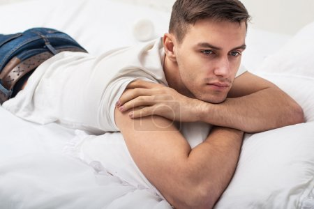 Photo for Handsome man guy in white T-shirt and blue jeans lying on a bed - Royalty Free Image