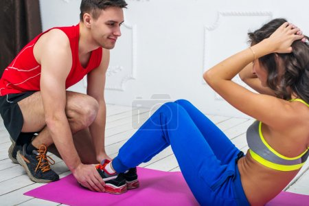Man helping a woman or girl in making abdominal crunch, exercises concept training exercising workout fitness aerobic