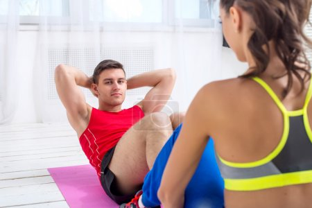 Active sportive man doing abdominal exercises crunches on floor in gym with the help of woman concept training exercising workout fitness aerobic