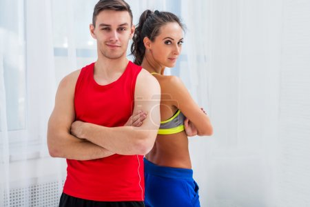 sporty couple friends slim athletic ambitious woman and confident man trainers team or coach client in sport hall gym standing arms crossed sportsmen professionals looking at camera