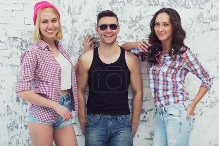 Photo for Friends two beautiful girls and handsome guy standing near a wall smile cheerfully - Royalty Free Image