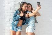 Two girls friends taking selfie together wearing jeans jackets and shorts summer jeanswear street urban casual style having fun.