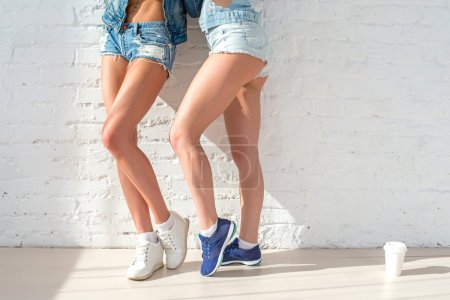 sporty long sexy legs of two beautiful women jeans shorts urban casual street style fashion sunny day standing near to the wall