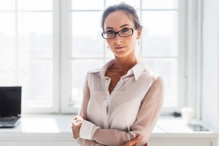 Photo for Serious young businesswoman in glasses standing front of the window background arms crossed - Royalty Free Image