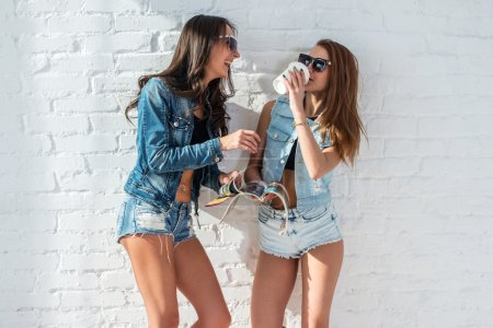 Two pretty girls wearing sunglasses in summer jeanswear street urban casual style talking, laughing having fun on the background of brick wall.