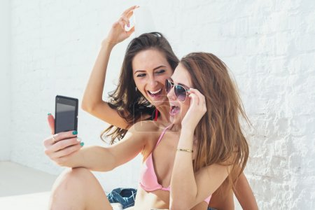 Female friends laughing having fun taking selfie together wearing bikini bra swimsuit summer sunny day street urban casual style