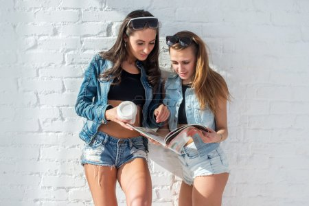 Two beautiful girls friends reading the magazine wearing sunglasses and denim jeans jackets shorts urban street casual style