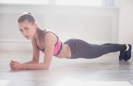 Slim fitnes young girl with ponytail doing planking exercise indoors in a sunlight.
