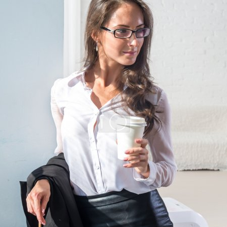 Woman in glasses with the cup of coffee or tea office
