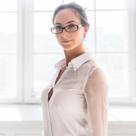 Photo pour Sérieux jeune femme d'affaires dans des verres debout avant de l'arrière-plan de la fenêtre - image libre de droit