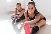 Skupina fit žen, pracovní protahování svalů nohou zpět do zahřát v posilovně fitness, sport, vzdělávání a životním stylu koncept