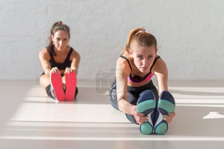 Two young women stretching reaching  with hands to toes seated forward bend warm up at gym fitness, sport, training and lifestyle concept.