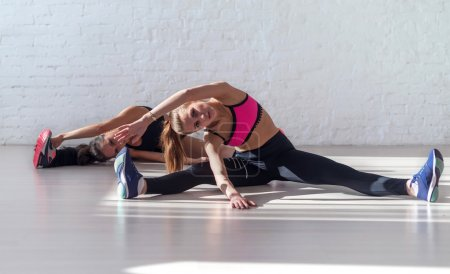 Two beautiful fitness slim  girls doing yoga stretching exercise tilts to side together sitting on the floor