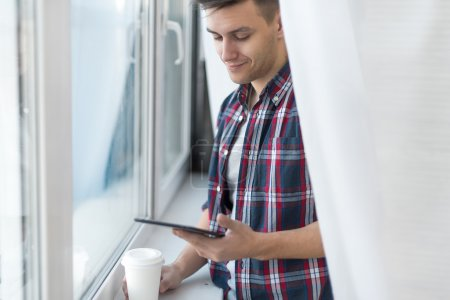 Handsome smiling man guy in plaid shirt near window with a cup of morning coffee and tablet