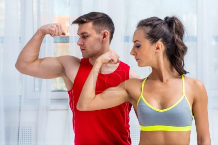 Photo for Active athletic sportive woman girl and man showing their muscles biceps healthy lifestyle - Royalty Free Image