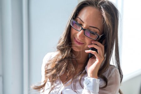 businesswoman smiling talking on the phone in front of window office